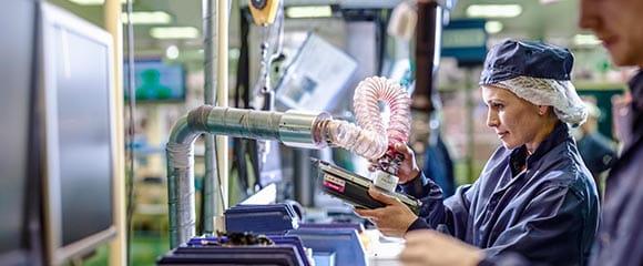 En person på en fakbrikk resirkulerer en brukt tonerkassett
