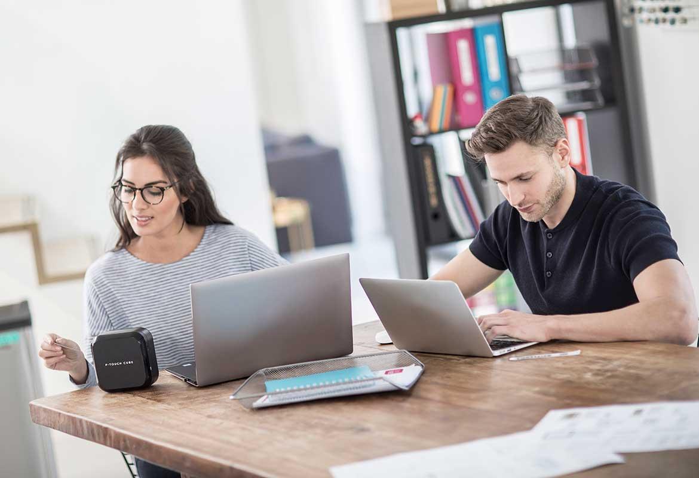 En mann og en dame på et moderne kontor bruker sine pc-er til å designe og skrive ut merkelapper på en Brother P-touch merkemaskin.