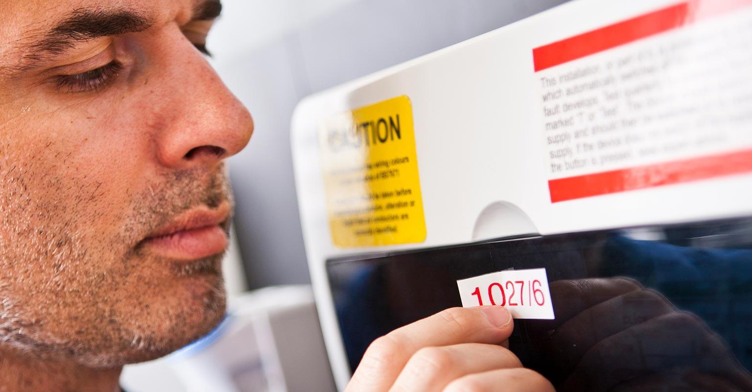 Mann setter en etikett på en vare