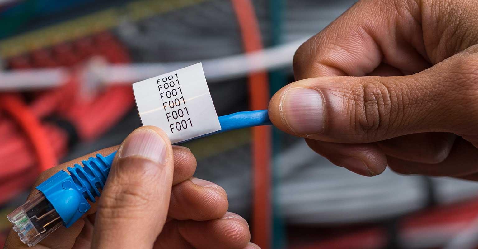 Brother TZe kabel etikett klar til å klistre rundt en nettverkskabel