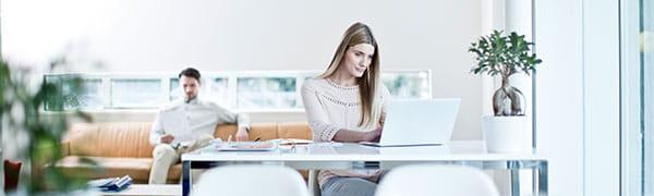 kvinne satt ved et skrivebord på en bærbar datamaskin