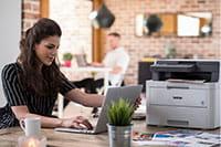 En dame med en DCPL3550CDW på skrivebordet