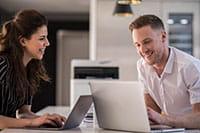 Mann og dame ved kontorpult og en støysvak DCPL3550CDW skriver