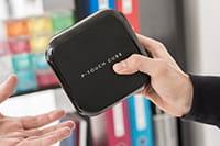 En person leverer fra seg Brother P-touch P710BT merkemaskin til en annen person