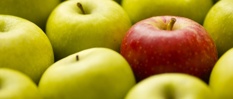 Ett rødt eple skiller seg ut mot et utvalg av grønne epler i en fruktkurv i en dagligvarebutikk