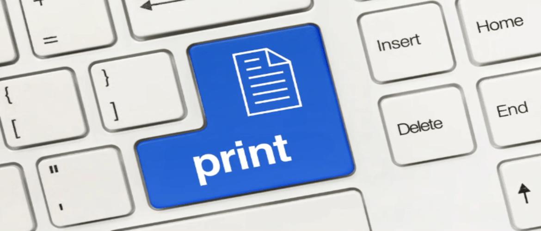 Et nærbilde av et standard QWERTY-tastatur med enter / print-tasten i blått med et dokumentikon og ordutskriften skrevet på den
