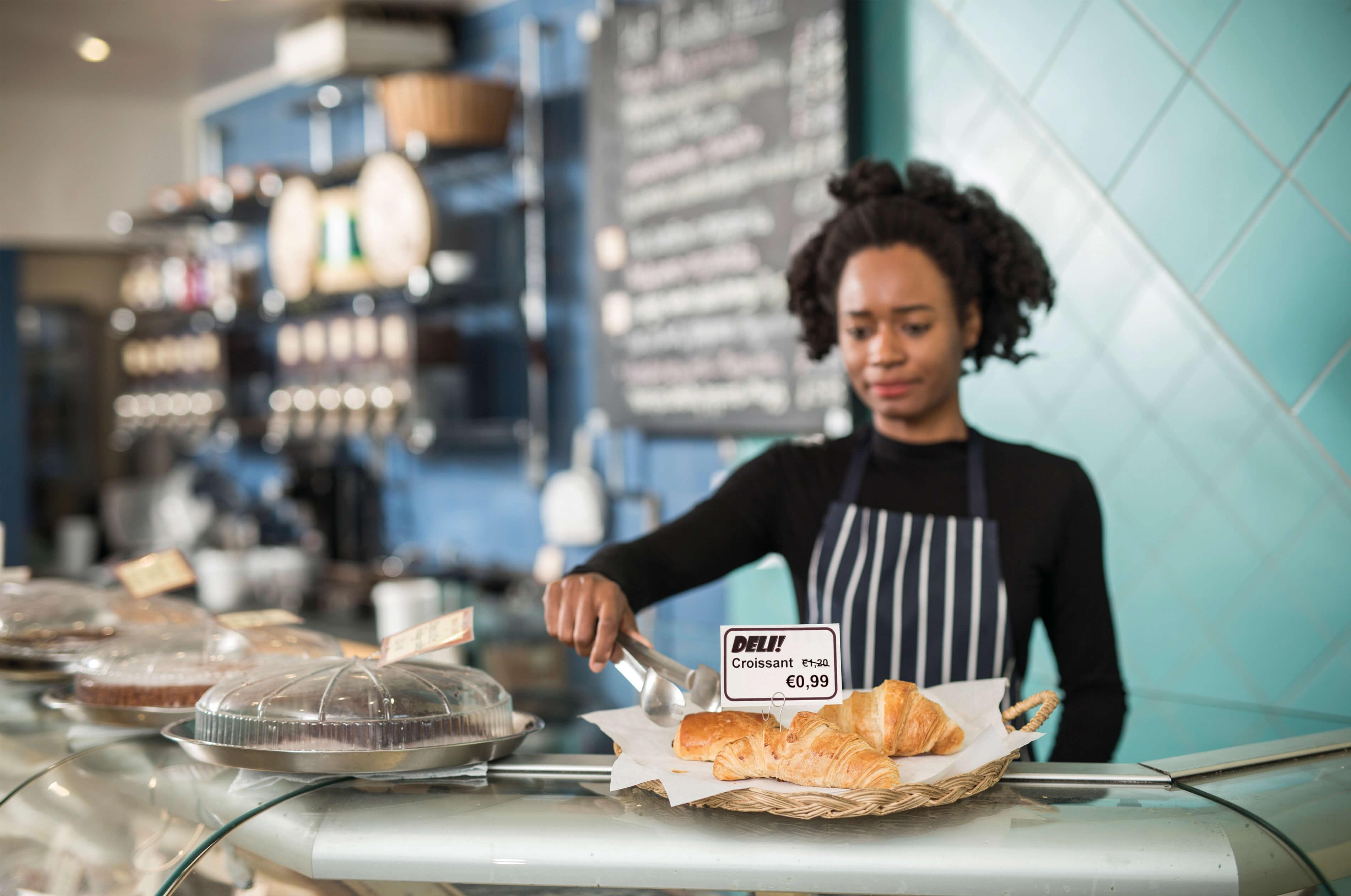 Kvinne bak en disk på en kafe