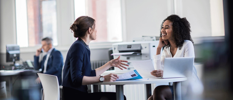 To kvinner har en samtale ved et skrivebord med en Brother blekkskriver i bakgrunnen