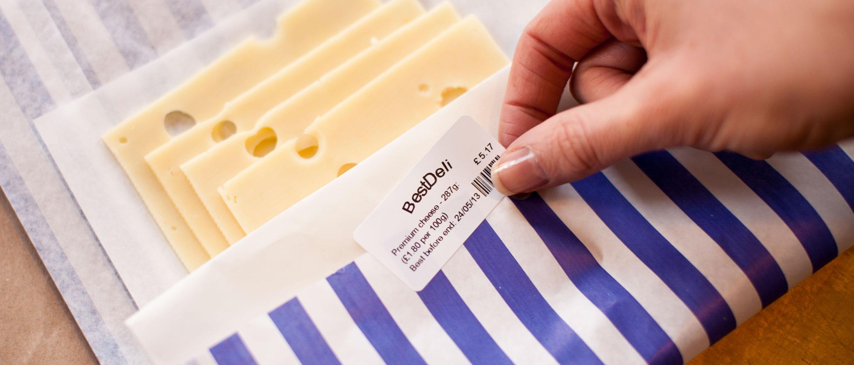 Etikett som klistres på en pakke med ost