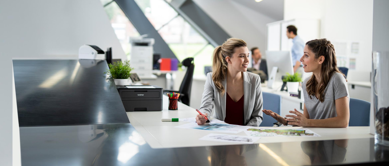 To kvinner sitter og snakker sammen på et travelt kontor. På pulten, penner og dokumenter, en skriver i bakgrunnents