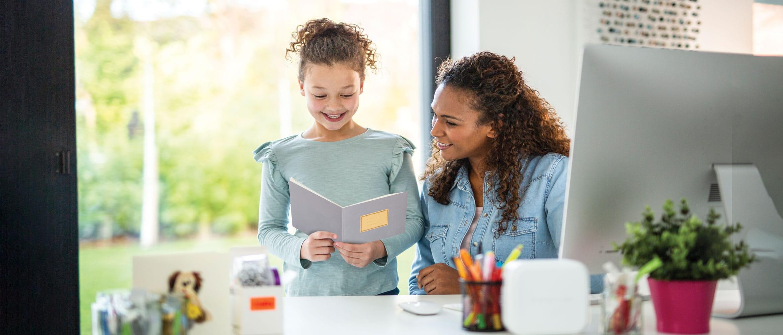 En kvinne og den lille jenta hennes har hjemmeskole og ler sammen mens de ser gjennom en arbeidsbok laget med Brothers Creative Center