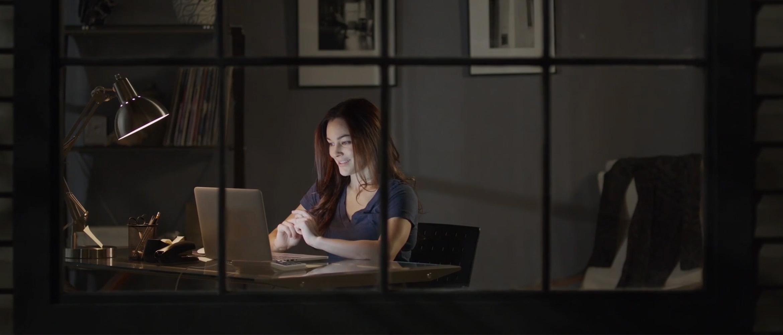 En kvinne sitter ved skrivebordet med en bærbar datamaskin om kvelden