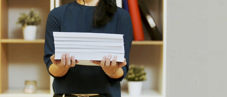 En kvinne holder en stor bunke dokumenter i hendene