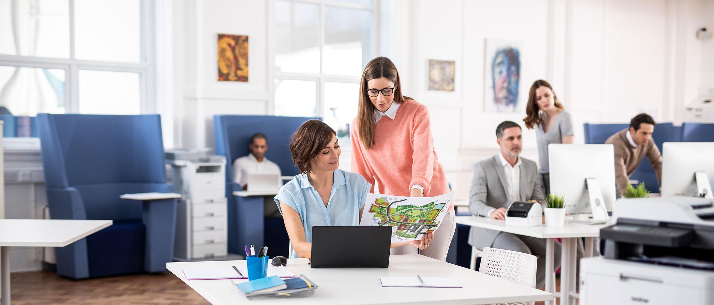 Kvinne som sitter ved en pc og en kvinne ved siden av som holder et dokument