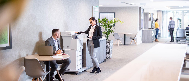 Mann sitter ved et bord og kvinne står ved en skriver i et kontorlandskap