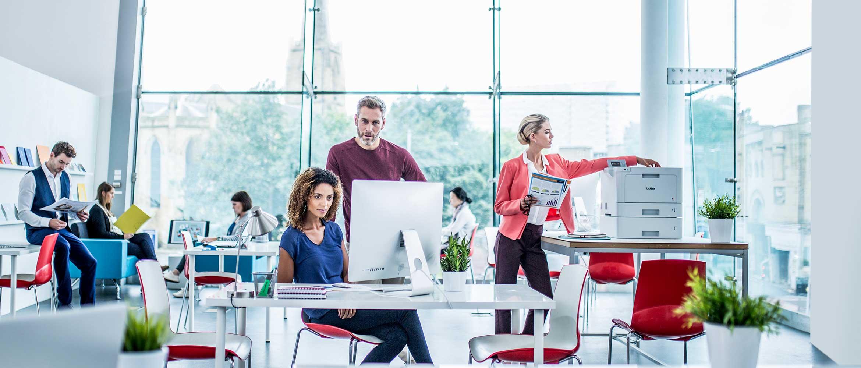Mann og kvinne diskuterer jobb i et kontormiljø