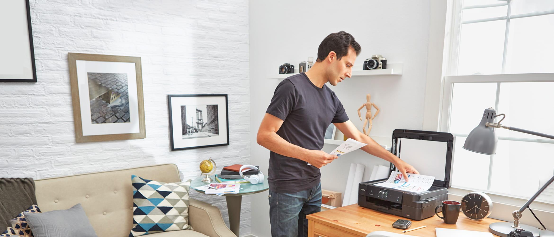 En mann på sitt hjemmekontor skanner dokumenter på en Brother multifunksjonsmaskin med skanner