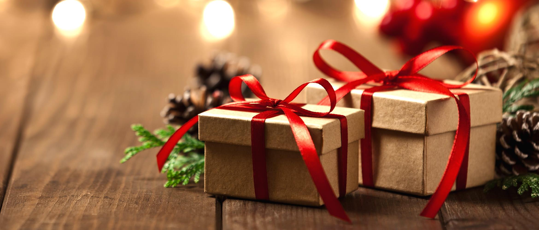 To julegaver i brune esker pyntet med røde silkebånd fra Brother med kongler i bakgrunnen