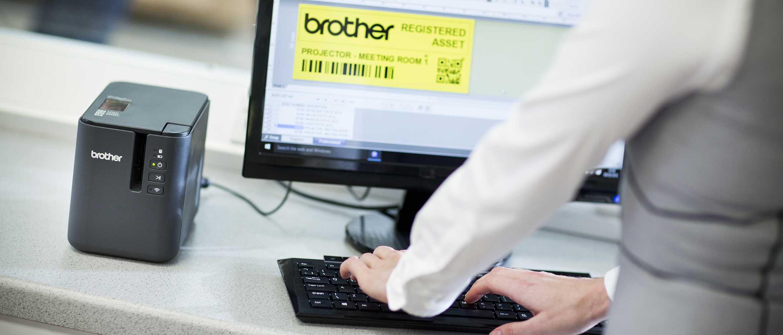 En person lager en etikett på en datamaskin for utskrift på en merkemaskin i Brother PTP900 serien