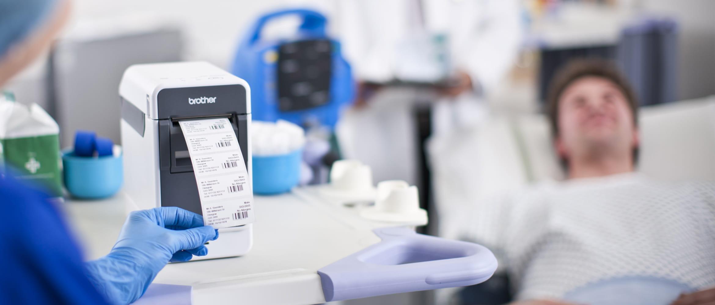 Sykepleier som skriver ut etiketter ved sykehussengen