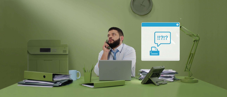 En mann sitter ved et skrivebord og snakker i telefonen
