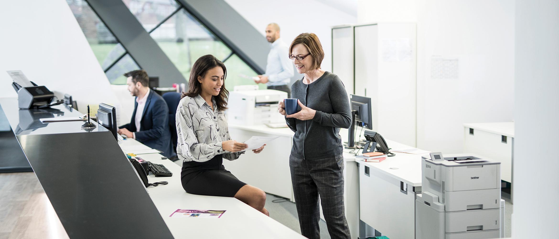 to kvinner diskuterer ved en kontorpult