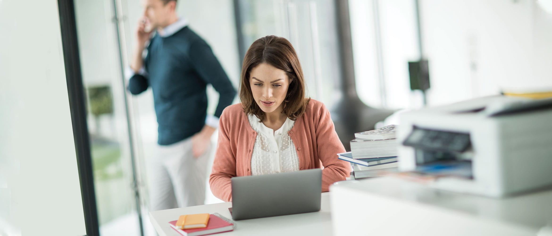 En kvinne jobber på hjemmekontoret på sin bærbare datamaskin og har en Brother skriver på bordet ved siden av seg. I bakgrunnen er en mann som snakker på mobiltelefonen sin.
