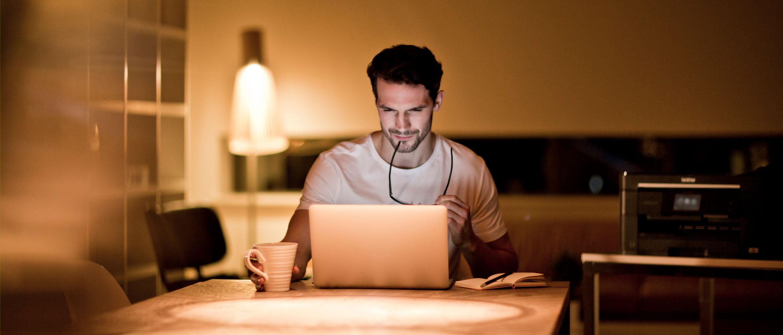 En mann sitter ved datamaskinen på hjemmekontoret og bestiller rekvisita. En Brother skriver står i bakgrunnen.