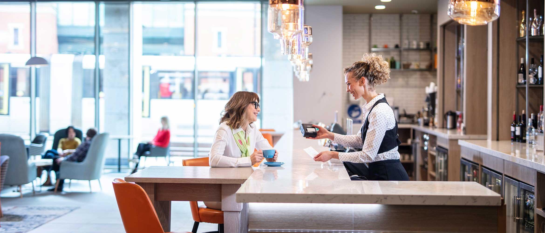 Kvinnelig betjening serverer en dame kaffe i en bar