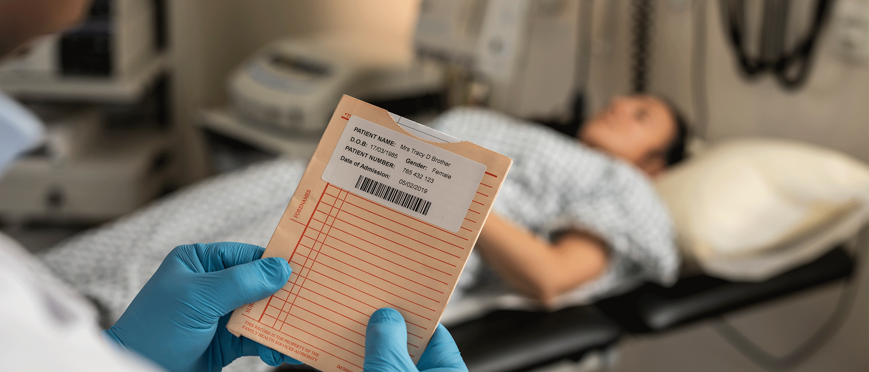 En sykehusansatt holder et dokument med en etikett med strekkoder, og en pasient ligger på et undersøkelsesbord i bakgrunnen