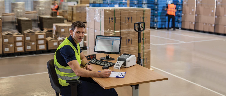 En person sitter ved et skrivebord på et lager med en pall med esker i bakgrunnen