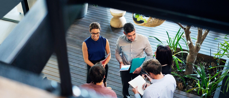 Fem ansatte (to kvinner og tre menn) på fremtidens arbeidsplass holder et uformelt stand-up forretningsmøte på kontoret sett ovenfra. Medarbeiderne i teamet holder filer, notisblokker og nettbrett mens de samarbeider.
