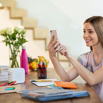 En kvinne sitter ved et bord og bruker sin smarttelefon for å skriver ut merkelapper via Bluetooth