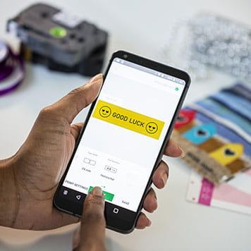 En person bruker sin smarttelefon for å designe og skrive ut merkelapper