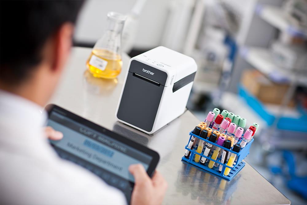 Laboratorietekniker merker prøver med et nettbrett og en mobil etikettskriver i Brother TD-serien