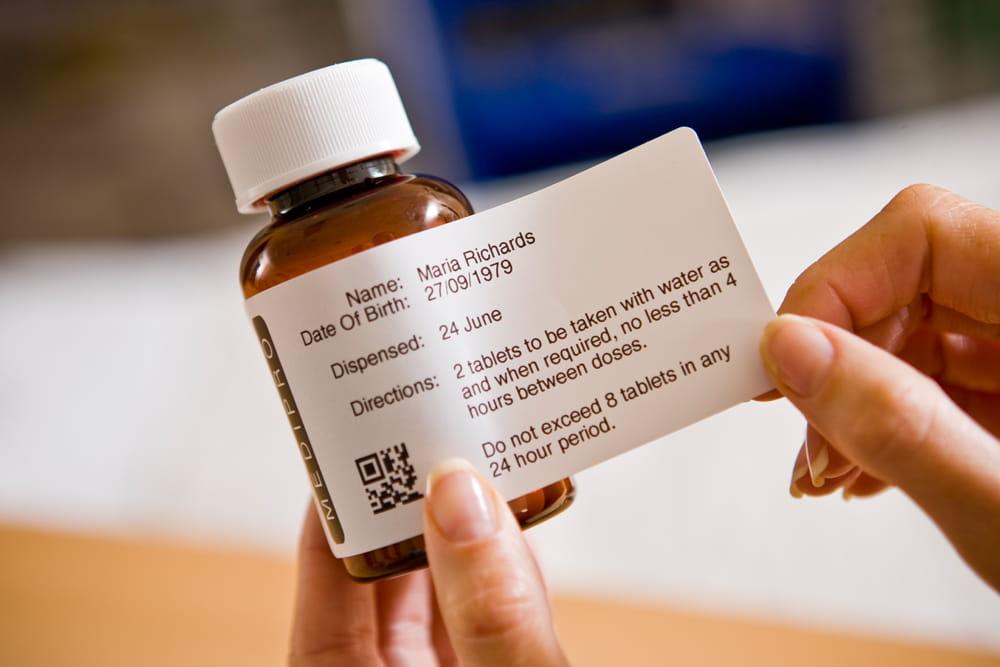 En etikett festes på en medisinflaske
