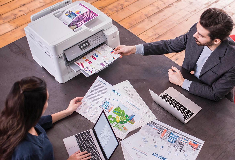 Mann og kvinne sitter ved et skrivebord med en blekkskriver som skriver ut fargedokumenter