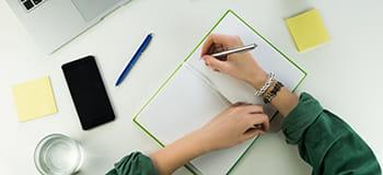 En kvinne skriver i en notatbok, en mobiltelefon, et glass vann, en  penn og post-it blokker ligger på skrivebordet