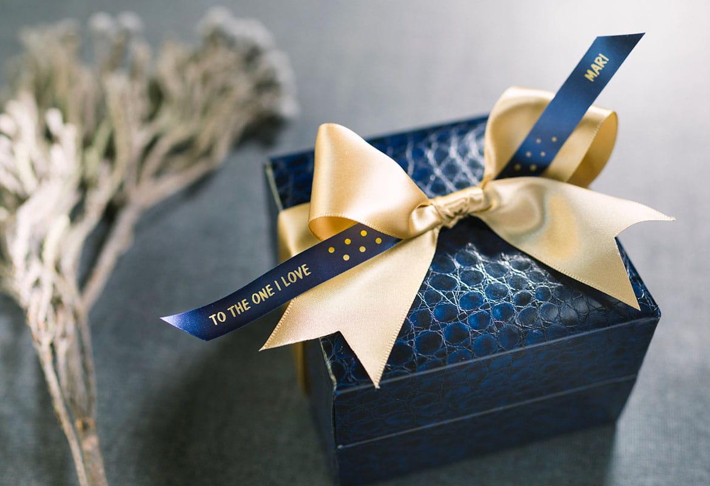 En blå gaveeske er pyntet med en gull sløyfe og Brother silkebånd i blått med gull tekst