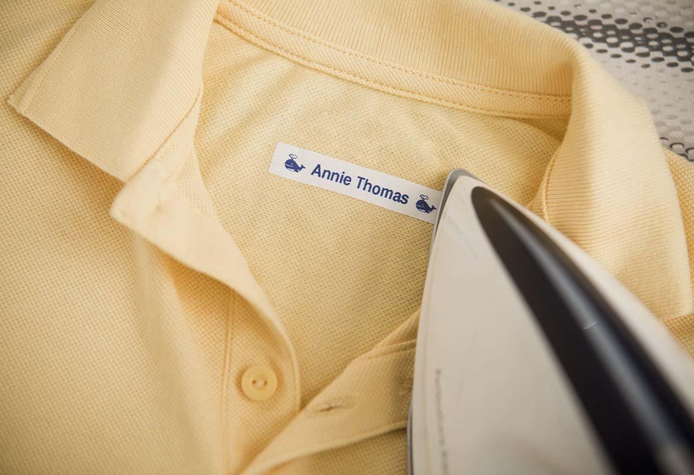 En poloskjorte er merket med en Brother stryke på tekstiltape som viser et barns navn