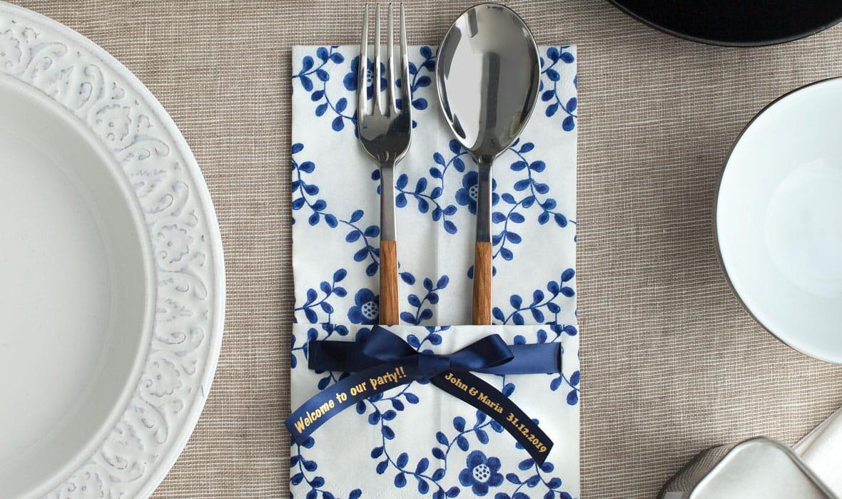 Et blått Brother silkebånd med en personlig beskjed festet på en serviett med bestikk