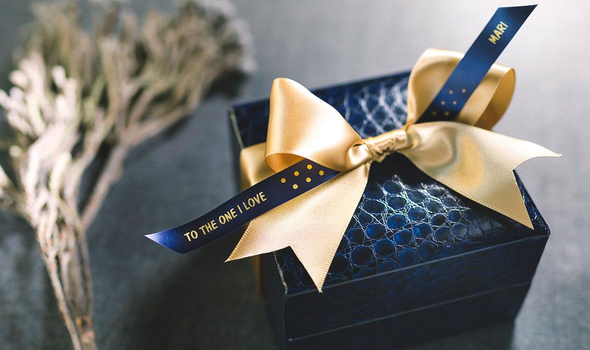 Bryllupsgaveeske personliggjort med et Brother silkebånd i marineblått med gullskrift