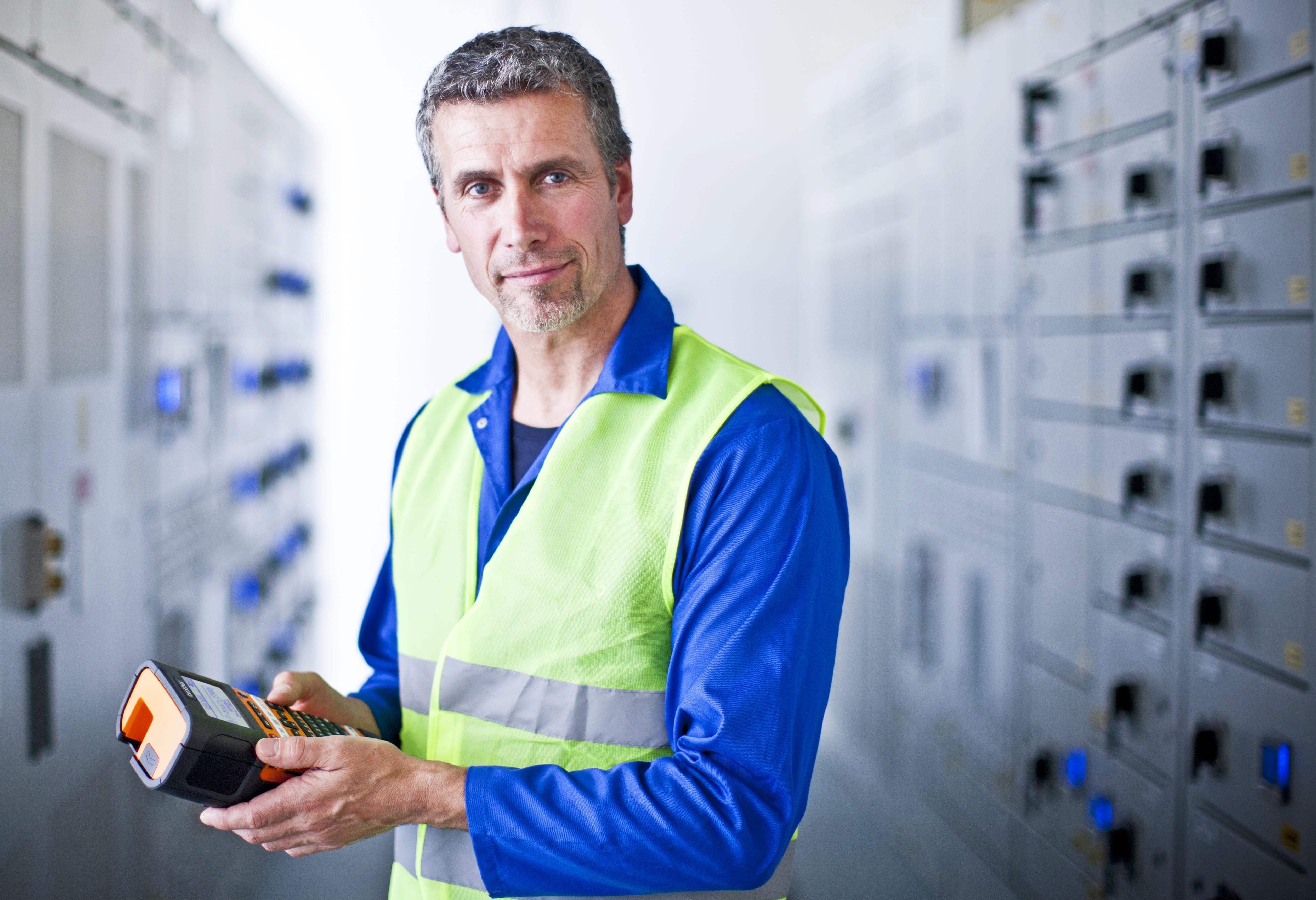 Mannlig elektriker holder en Brother PT-E550W etikettskriver