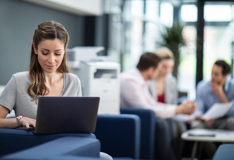 Dame i sofa med bærbar datamaskin og mennesker som sitter i et møte i bakgrunnen