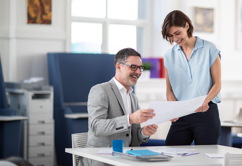 Mann og kvinne snakker sammen i et kontorlandskap