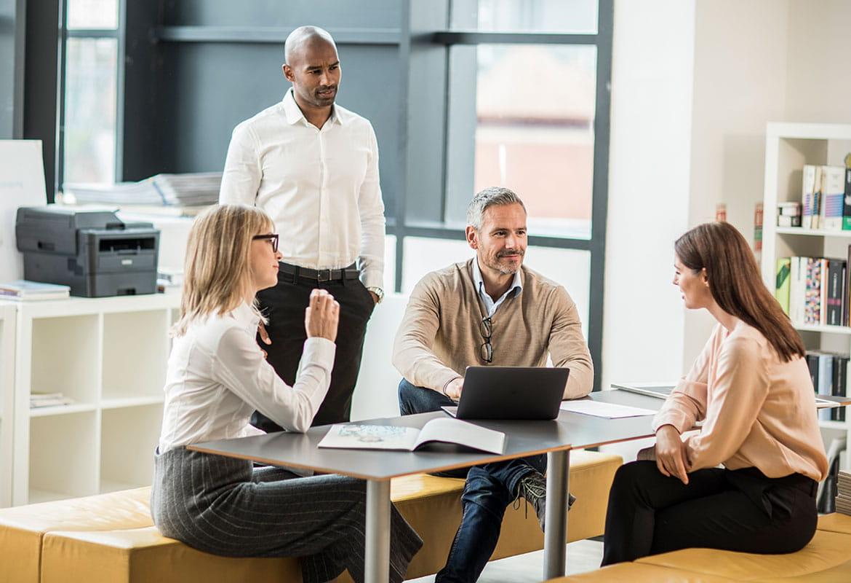 To menn og to kvinner som står og sitter rundt et bord og snakker sammen