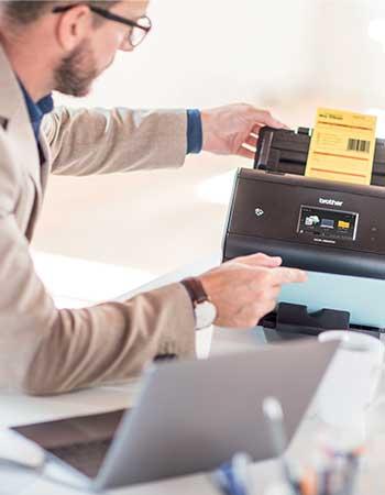 Mann skanner dokument med strekkode på en skanner med Brother Barcode Utility programvare