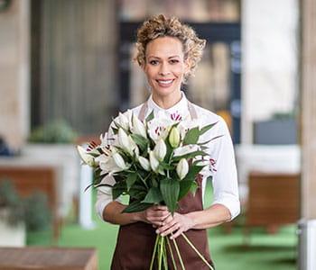En butikkansatt holder en blomsterbukett i hånden i en blomsterbutikk