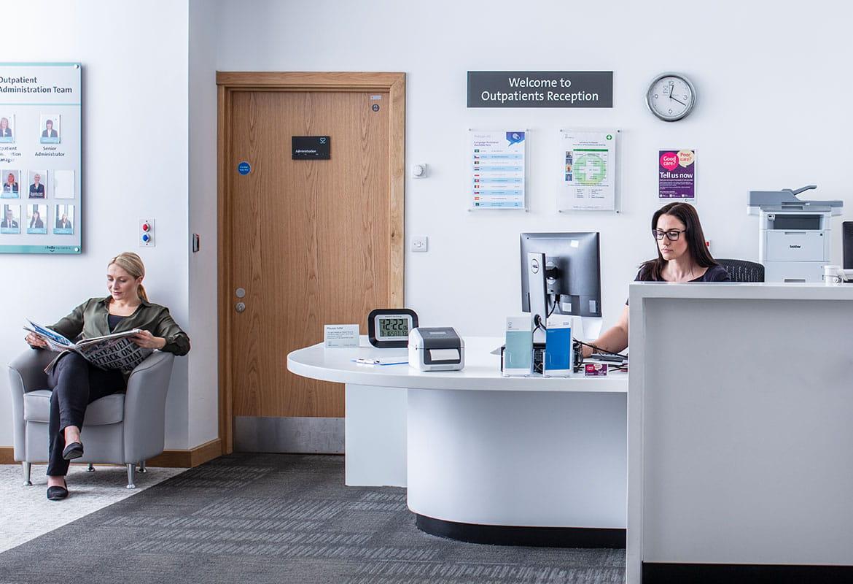 Kvinnelig resepsjonist sitter ved skrivebordet å jobber på en datamaskin, kvinnelig pasient sitter og leser avisen