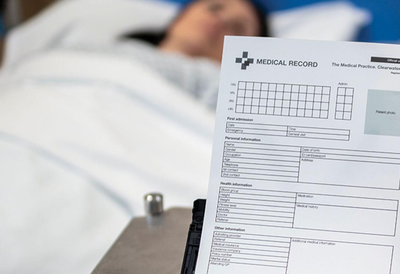 Kvinnelig pasient som ligger i sengen, Brother ADS-3600W skanner som skanner et pasient dokument